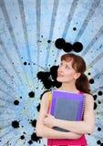 Mujer joven del estudiante que sostiene los cuadernos contra fondo salpicado azul Fotografía de archivo