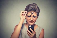 Mujer joven del Headshot con los vidrios que tienen problema que ve el teléfono celular Fotos de archivo