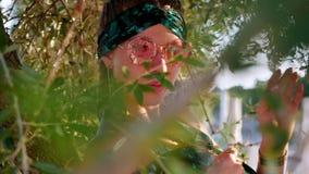 Mujer joven del hippie con las gafas de sol que se sientan en el árbol almacen de metraje de vídeo