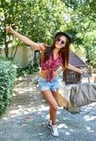 Mujer joven del inconformista con el sombrero y las gafas de sol al aire libre Fotos de archivo libres de regalías