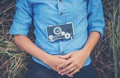 Mujer joven del inconformista con la cámara del vintage que se acuesta en outd del campo Fotografía de archivo