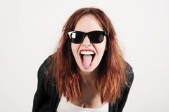 Mujer joven del inconformista de la belleza que grita y que muestra la lengua, cara divertida con las gafas de sol Foto de archivo libre de regalías