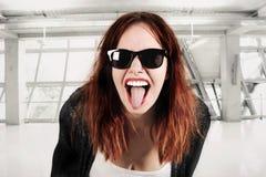 Mujer joven del inconformista de la belleza que grita y que muestra la lengua, cara divertida con las gafas de sol Imagen de archivo