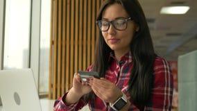 Mujer joven del inconformista de la raza mixta que sostiene la tarjeta de crédito y que usa el ordenador portátil metrajes
