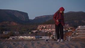 Mujer joven del inconformista en la playa con el animal doméstico del perro almacen de metraje de vídeo