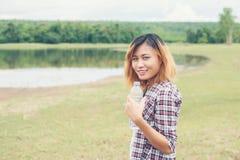mujer joven del inconformista que celebra la botella de agua en el parque del verde del verano Fotos de archivo libres de regalías