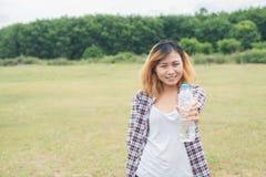 mujer joven del inconformista que celebra la botella de agua en el parque del verde del verano Imagen de archivo libre de regalías