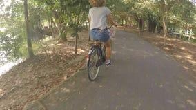 Mujer joven del inconformista que completa un ciclo en la bicicleta vieja del vintage en parque de la ciudad HD, Gopro a cámara l metrajes