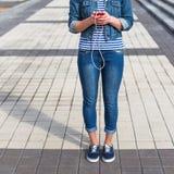 Mujer joven del inconformista que escucha la música en la ciudad Fotos de archivo libres de regalías