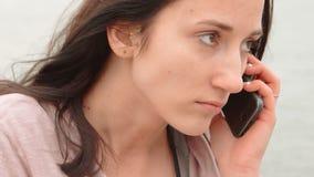 Mujer joven del inconformista que hace la conversación telefónica, cara seria, tono del color del vintage Mujer joven linda con e almacen de metraje de vídeo