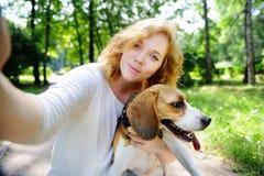 Mujer joven del inconformista que hace la foto del selfie con el perro del beagle imágenes de archivo libres de regalías