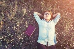 Mujer joven del inconformista que miente en campo de flor después de que ella cansara para el re Fotografía de archivo