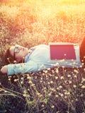 Mujer joven del inconformista que miente en campo de flor después de que ella cansara para el re Imagen de archivo libre de regalías