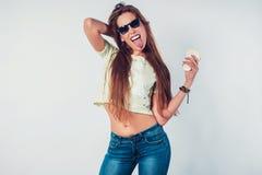 Mujer joven del inconformista que muestra la lengua con las gafas de sol Fotos de archivo