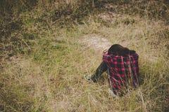 Mujer joven del inconformista que se sienta con la cabeza abajo en las rodillas tristes y solitarias Imágenes de archivo libres de regalías