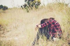 Mujer joven del inconformista que se sienta con la cabeza abajo en las rodillas tristes y solitarias Fotografía de archivo