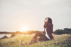 Mujer joven del inconformista que se sienta en hierba cerca del enjo relajante del lago fotografía de archivo