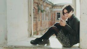 Mujer joven del inconformista que se sienta en un travesaño de la ventana en un edificio viejo Usando el teléfono celular metrajes