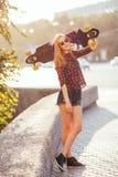 Mujer joven del inconformista que sostiene el monopatín detrás de la cabeza en puesta del sol, al aire libre, estilo cinemático M Fotografía de archivo