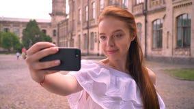 Mujer joven del jengibre hermoso con los hombros desnudos que toman el selfie con su teléfono y sonrisa, colocándose en la calle  metrajes