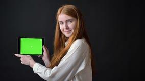 Mujer joven del jengibre que muestra los pulgares hasta la tableta con chromakey y que cabecea, sonriendo, aislado en fondo negro almacen de video