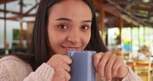 Mujer joven del Latino que goza de la taza de café caliente en café Fotos de archivo