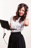 Mujer joven del negocio que trabaja en el ordenador portátil y que escucha la música en h Imagen de archivo libre de regalías