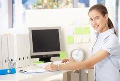 Mujer joven del oficinista en el escritorio Fotos de archivo