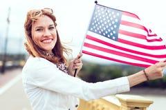 Mujer joven del patriota con la sonrisa dentuda que estira la bandera spangled estrella imagenes de archivo
