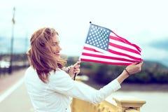 Mujer joven del patriota con la sonrisa dentuda que estira la opinión del perfil de la bandera de los E.E.U.U. foto de archivo