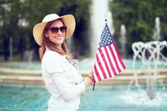 Mujer joven del patriota en smilig y sostener del sombrero la bandera de los E.E.U.U. en parque foto de archivo libre de regalías