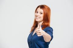Mujer joven del pelirrojo atractivo alegre que muestra los pulgares para arriba Imagenes de archivo