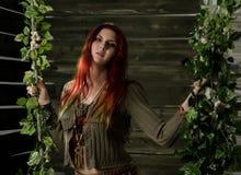 Mujer joven del pelirrojo del boho del hippie que se divierte en un oscilación Estilo del hippie en un fondo de madera Fotografía de archivo libre de regalías