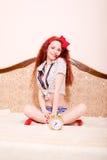 Mujer joven del pelirrojo del sexi feliz que se relaja en el sofá Imagenes de archivo