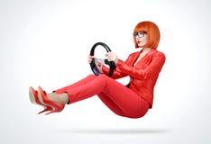 Mujer joven del pelirrojo en coche rojo del conductor del traje con el volante, concepto auto Imagen de archivo libre de regalías