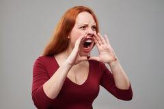 Mujer joven del pelirrojo enojado que grita en alta voz Imagenes de archivo