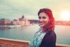 Mujer joven del pelirrojo que presenta en Budapest en puesta del sol foto de archivo