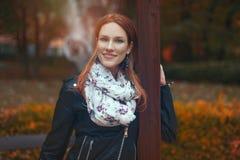 Mujer joven del pelirrojo que presenta en parque en el otoño Foto de archivo