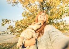 Mujer joven del pelirrojo que toma el selfie sorprendido al aire libre con el perro Imagen de archivo libre de regalías