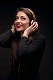 Mujer joven del pelo largo feliz hermoso que escucha la música en wir Foto de archivo libre de regalías