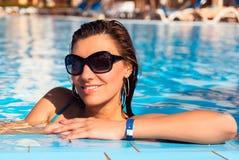 Mujer joven del pelo largo hermoso en el agua azul en gafas de sol, cierre encima del retrato al aire libre Foto de archivo libre de regalías