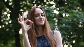 Mujer joven del pelo largo que dice muy bien con su mano en un parque Foco en la muchacha almacen de metraje de vídeo