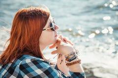 Mujer joven del pelo rojo hermoso en gafas de sol en la playa Foto de archivo