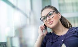 Mujer joven del placer en el teléfono Imágenes de archivo libres de regalías