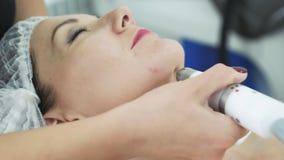 Mujer joven del primer en procedimiento hidratante, antienvejecedor y de elevación facial en clínica de la cosmetología metrajes