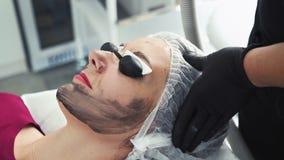 Mujer joven del primer en vidrios protectores en la cara de carbono que pela procedimiento en clínica de la cosmetología almacen de video