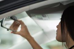 Mujer joven del primer que se sienta en el coche que ajusta el espejo, según lo visto de ángulo del perfil, concepto femenino del Fotografía de archivo libre de regalías
