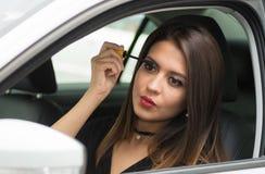 Mujer joven del primer que se sienta en el coche que pone en el maquillaje que mira en espejo, según lo visto de la ventana exter Imagen de archivo