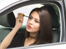 Mujer joven del primer que se sienta en el coche que pone en el maquillaje que mira en espejo, según lo visto de la ventana exter Foto de archivo libre de regalías