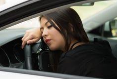 Mujer joven del primer que se sienta en obrar recíprocamente del coche cansado y dormir, según lo visto de ventana exterior de lo Fotografía de archivo